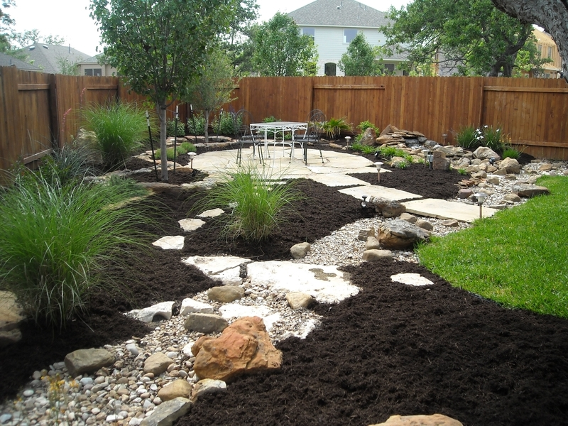 Backyard dry creek bed landscaping ideas that incorporate low maintenance plants